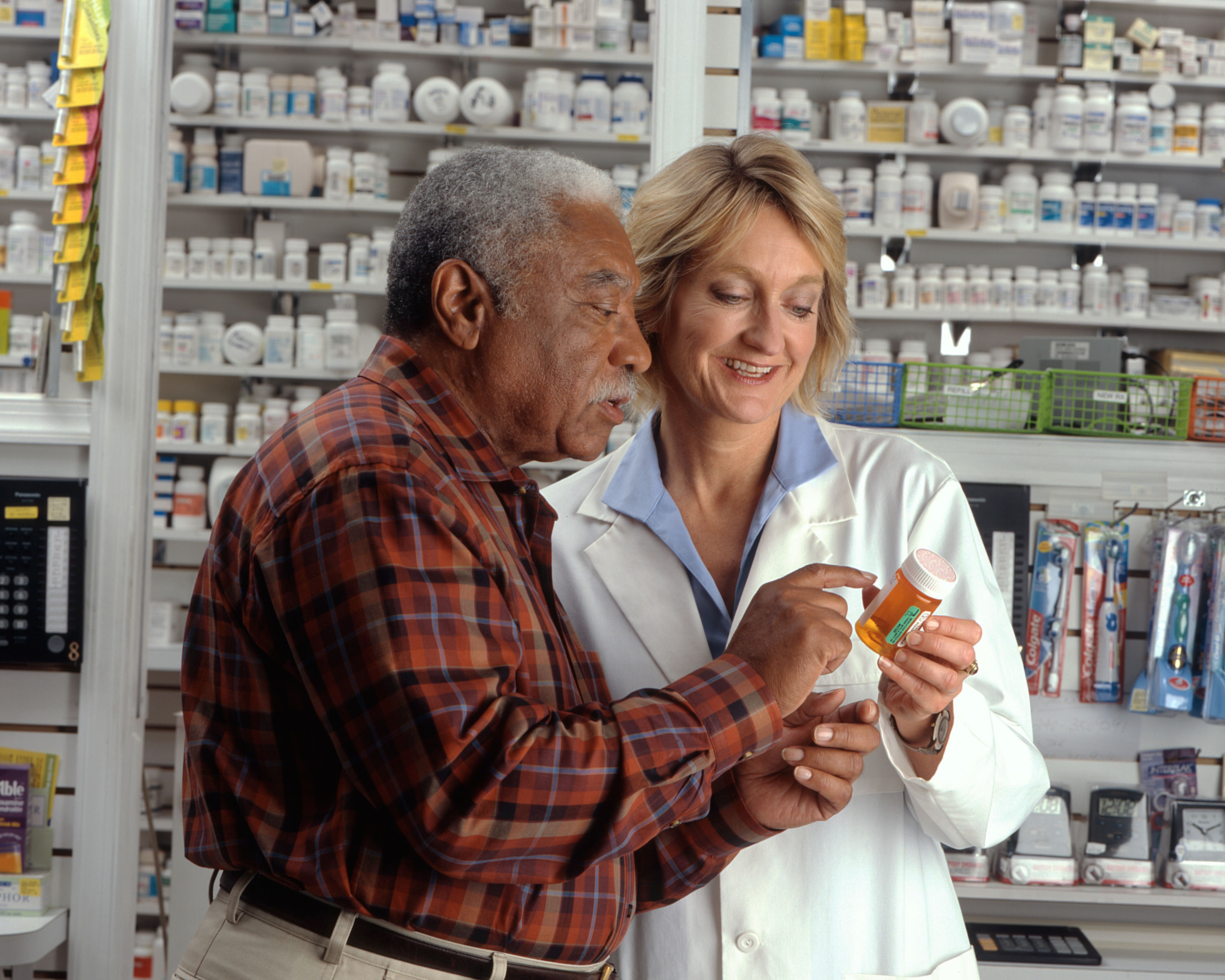 A doctor looks over a prescription bottle with her patient