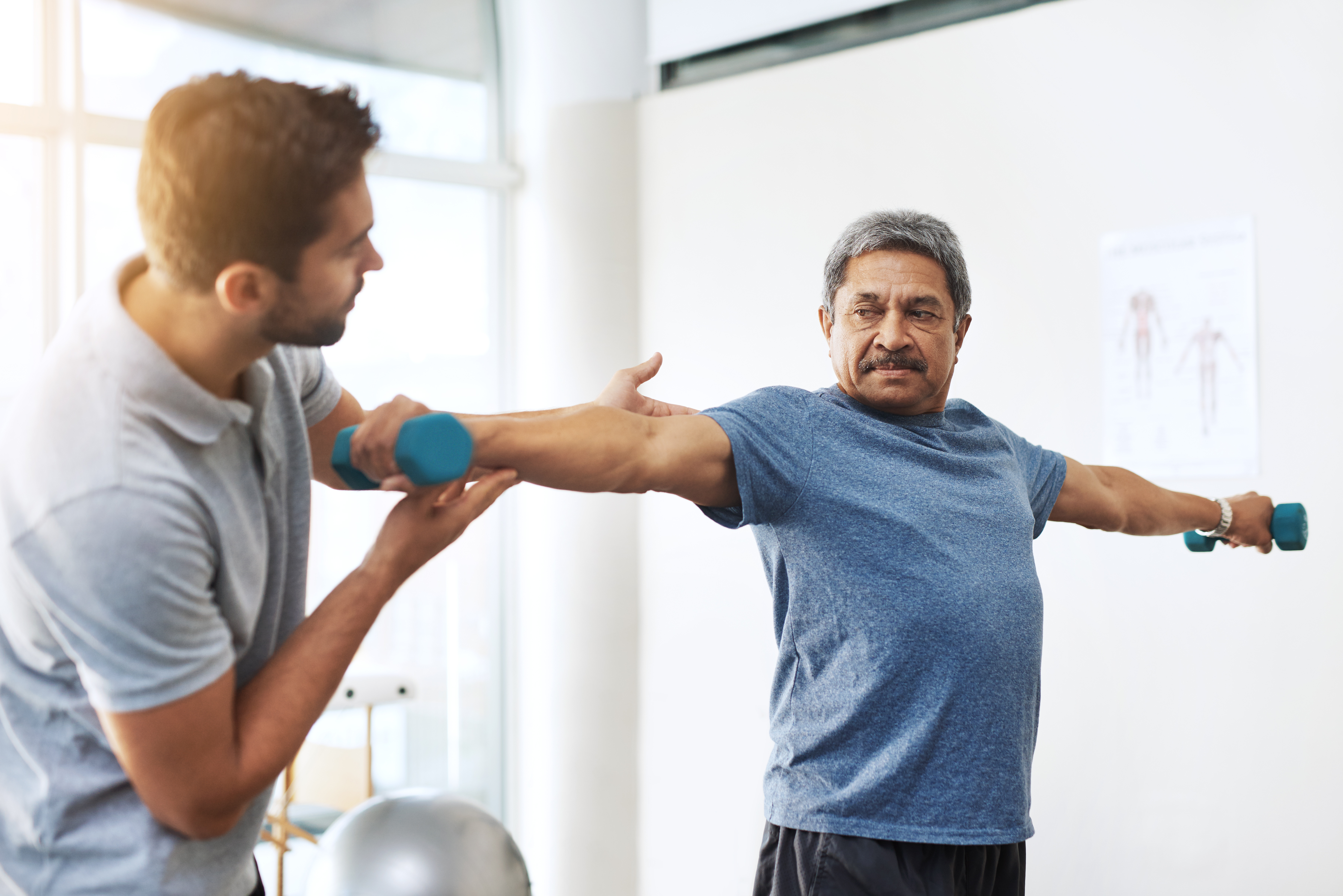 An older man is going through physical therapy using light weights with his physical  therapist