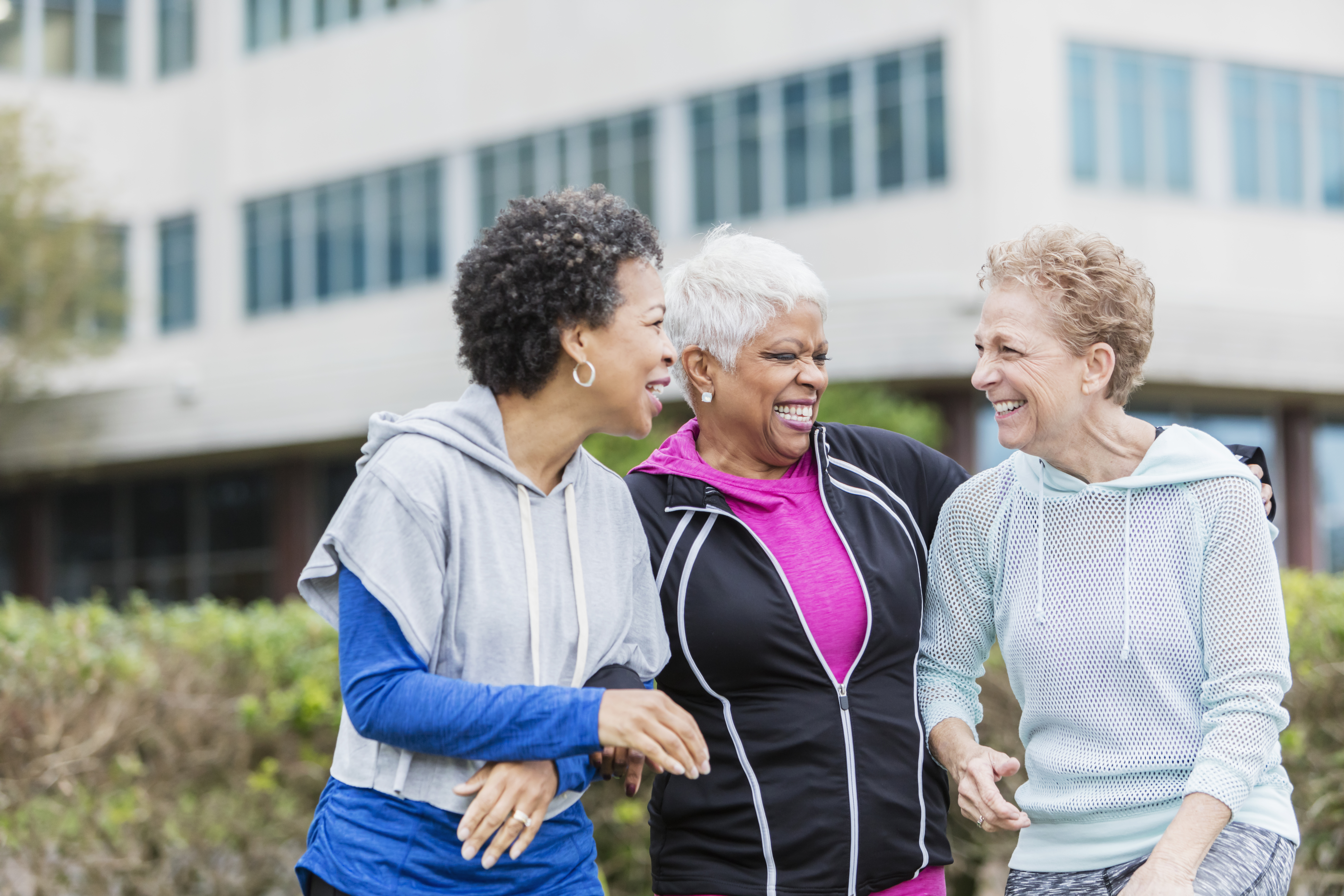 Three older women laughing and talking while exercising outside