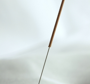 Acupuncture needle stuck in white cloth